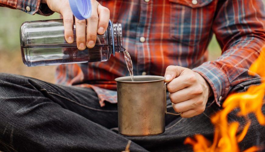 Mann am Lagerfeuer gießt sich Wasser in einen Becher