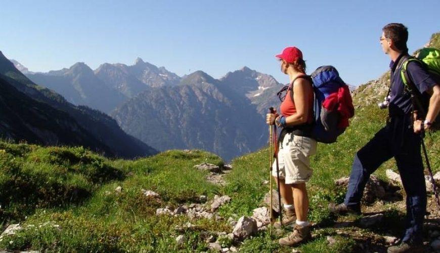Teilnehmerin einer Alpenüberquerung genießt den Blick