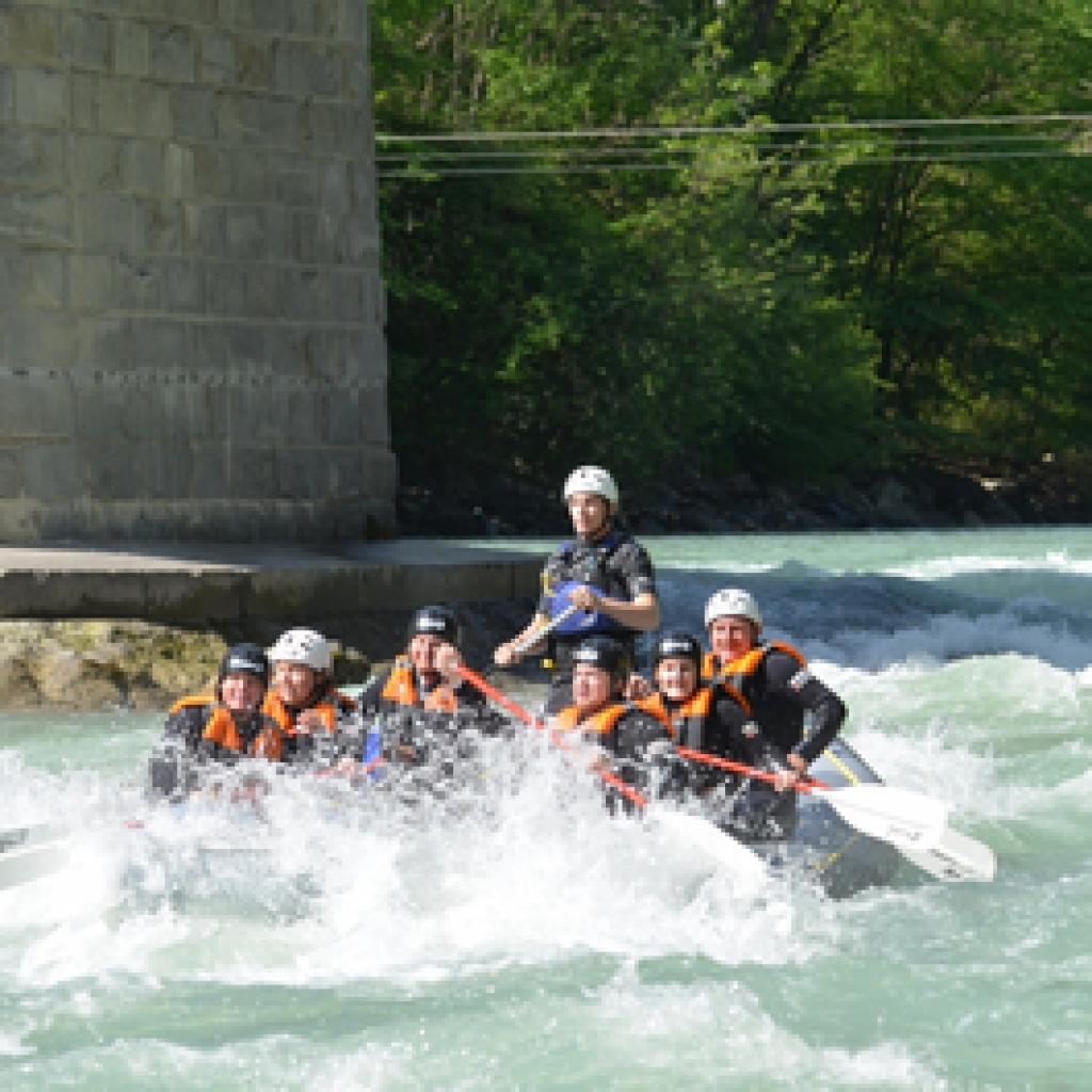 Schlauchboot fährt beim Rafting unter einer Brücke durch
