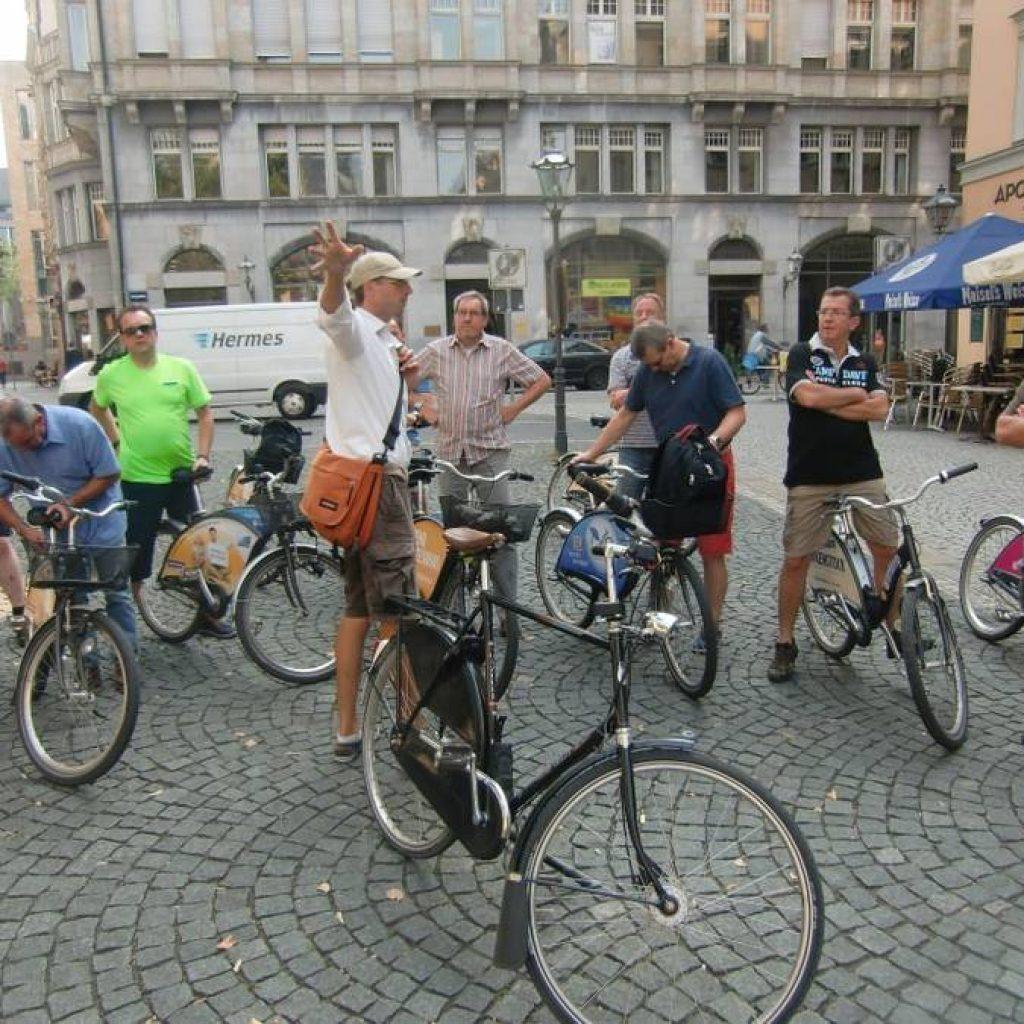 Gruppe Radfahrer hört dem Guide auf einem Platz zu