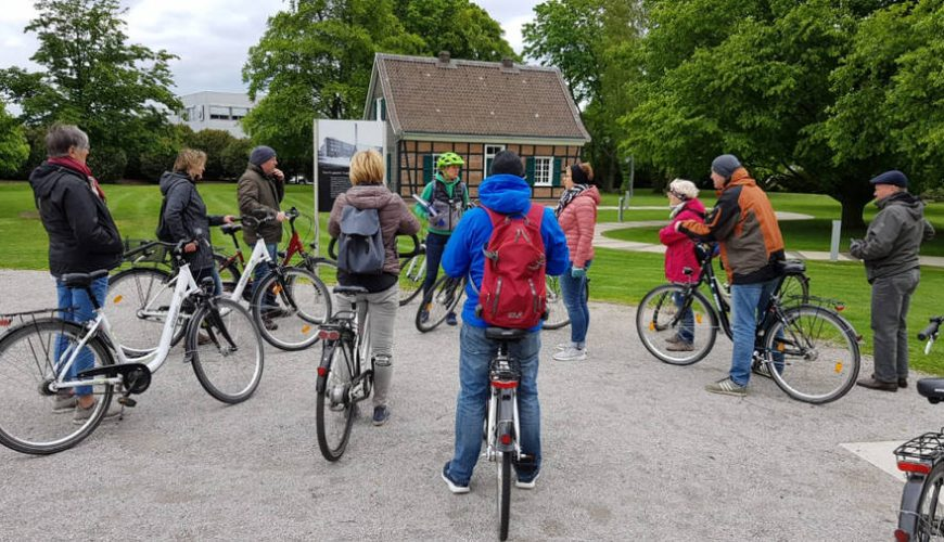 Radfahrer hören ihrem Guide bei einer Pause in einem Park zu