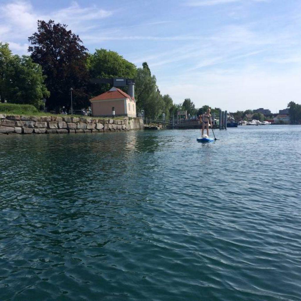 Frau macht Stand Up Paddling auf dem Bodensee