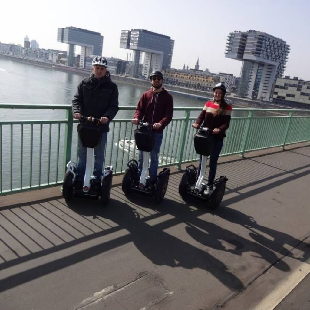 Drei Segway Fahrer in Köln auf einer Brücke vor den Kranhäusern