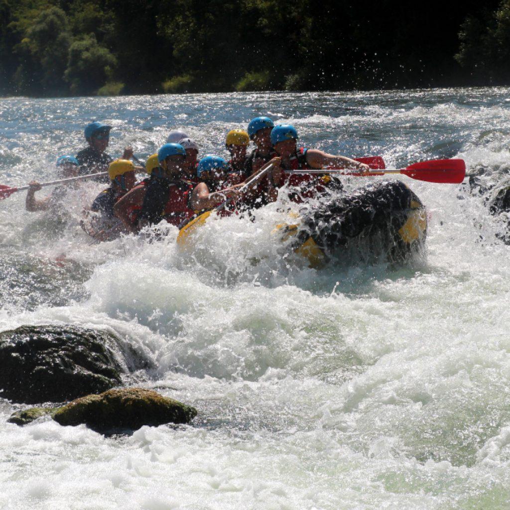 Schlauchboot wird von Wellen beim Rafting auf dem Rhein erfasst