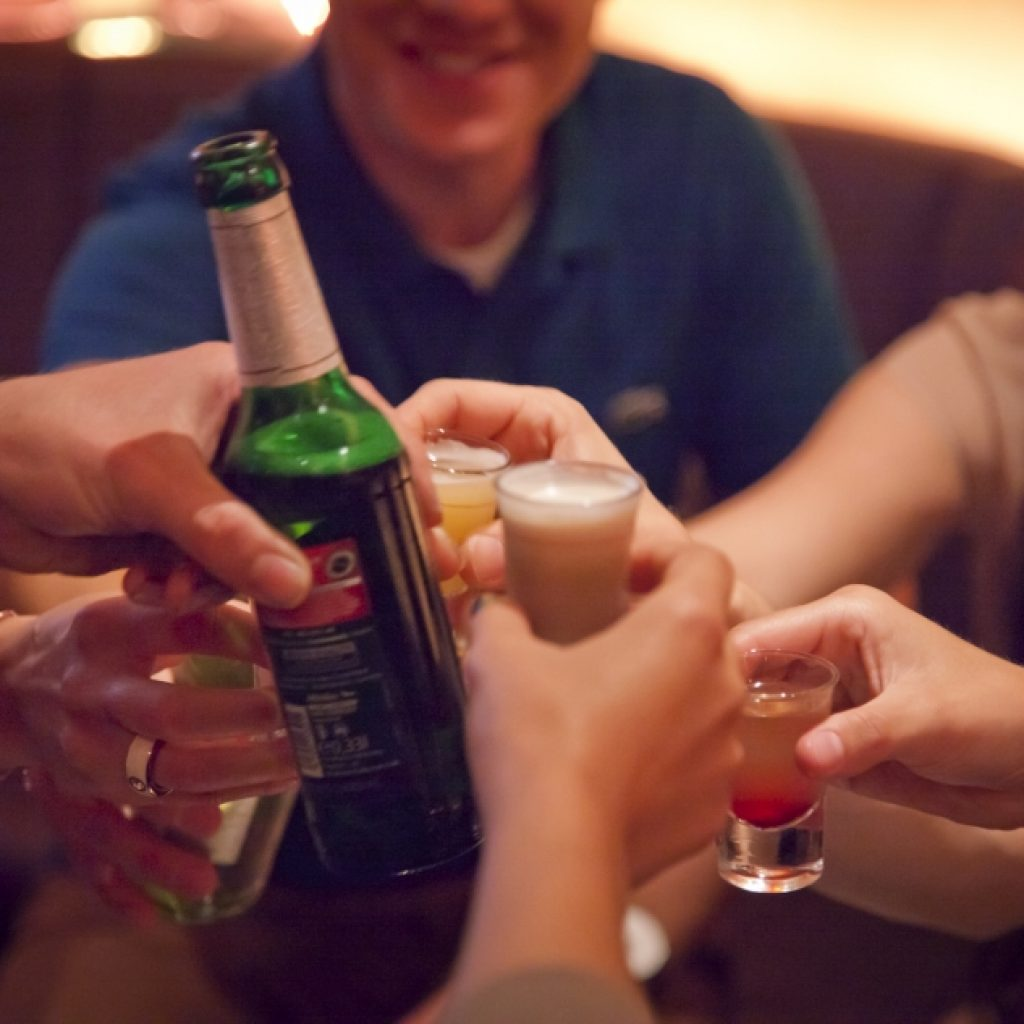 Menschen prosten sich mit Bier und Schnaps zu