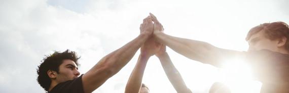 Menschen stehen im Kreis und berühren sich mit den Händen über dem Kopf