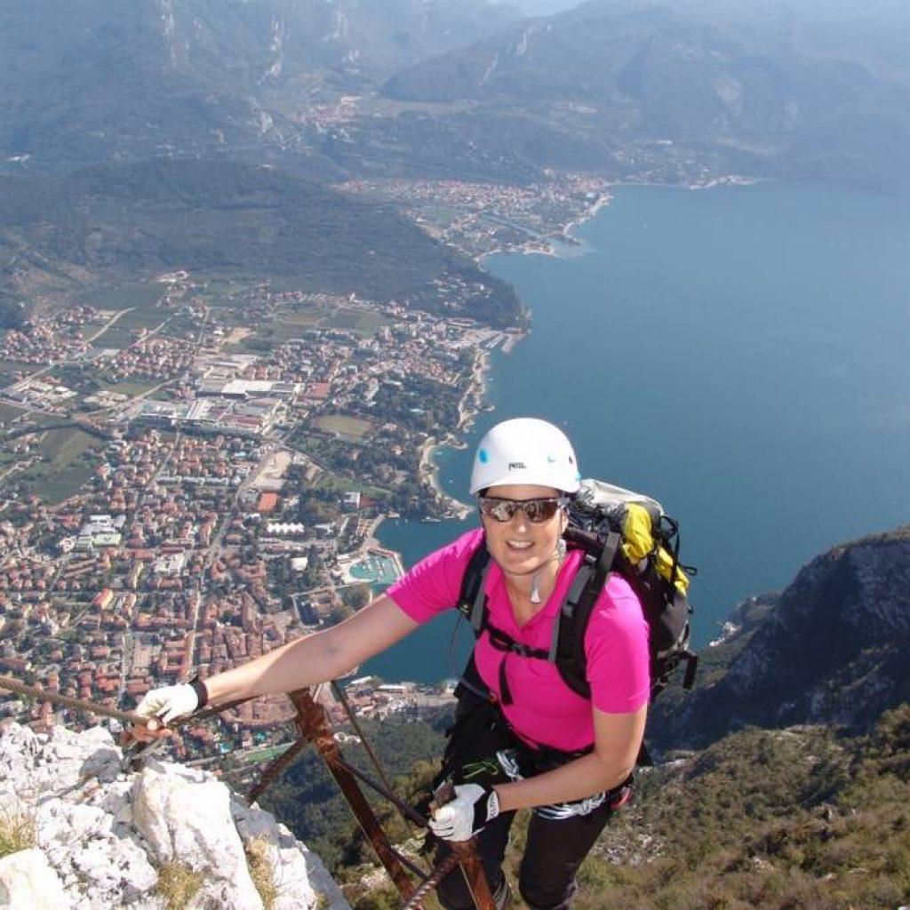 Klettererin am Fels vor dem Gardasee