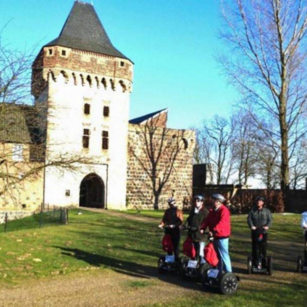 Segwayfahrer vor mittelalterlichem Turm