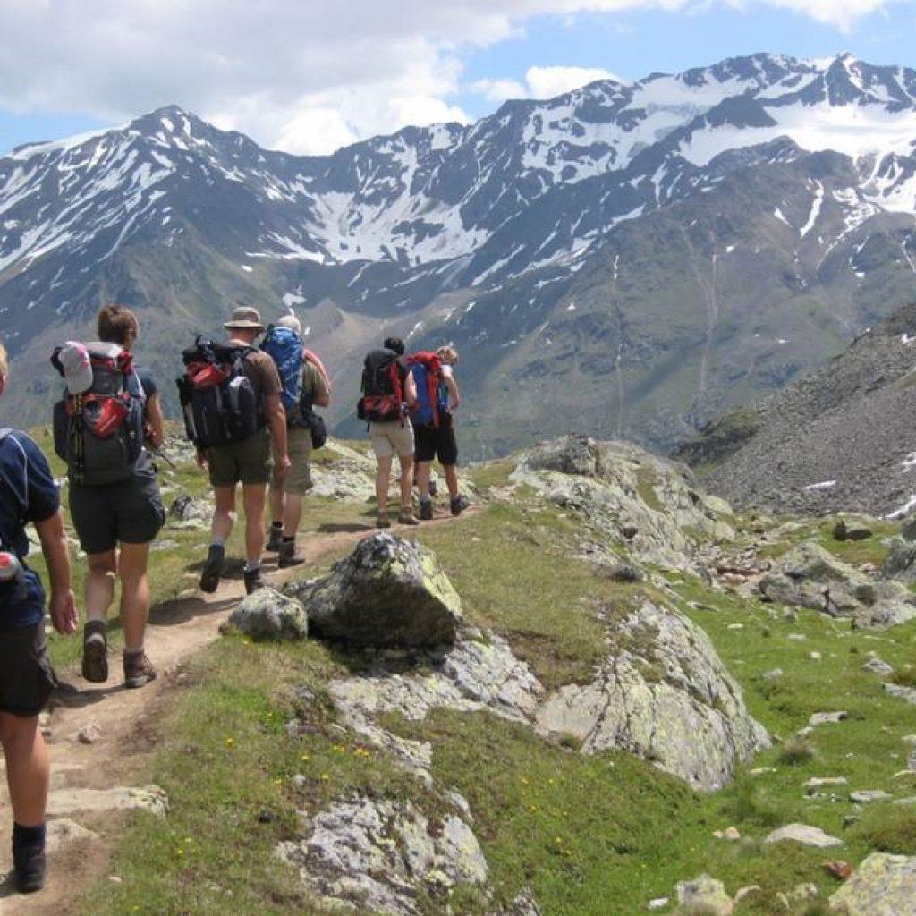 Teilnehmer einer Alpenüberquerung mit Gepäcktransport