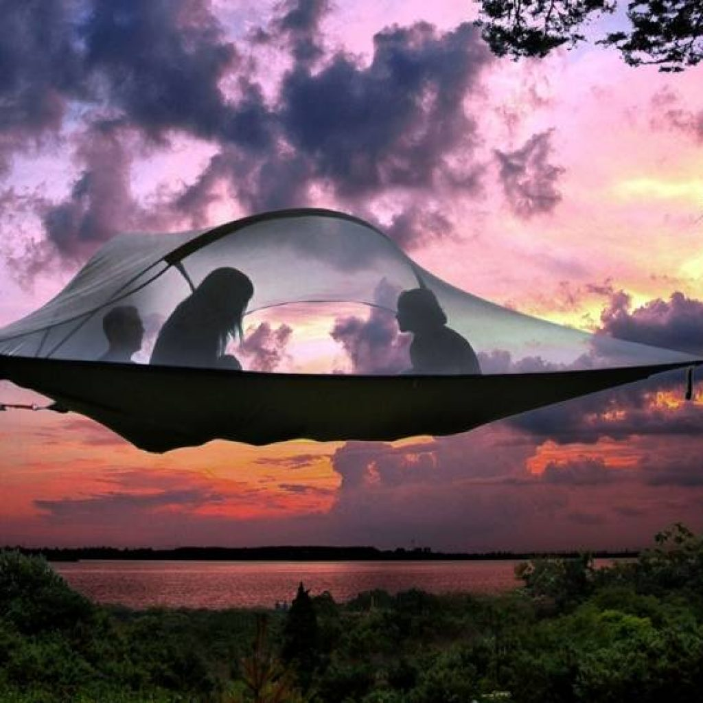 Drei Menschen im Baumzelt bei Sonnenuntergang