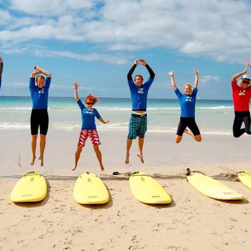 Surfer springen vor ihren Boards in die Luft