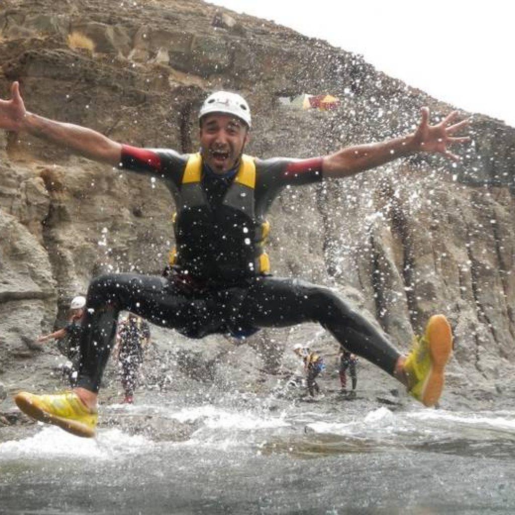 Mann springt vor Freude in die Luft beim Canyoning