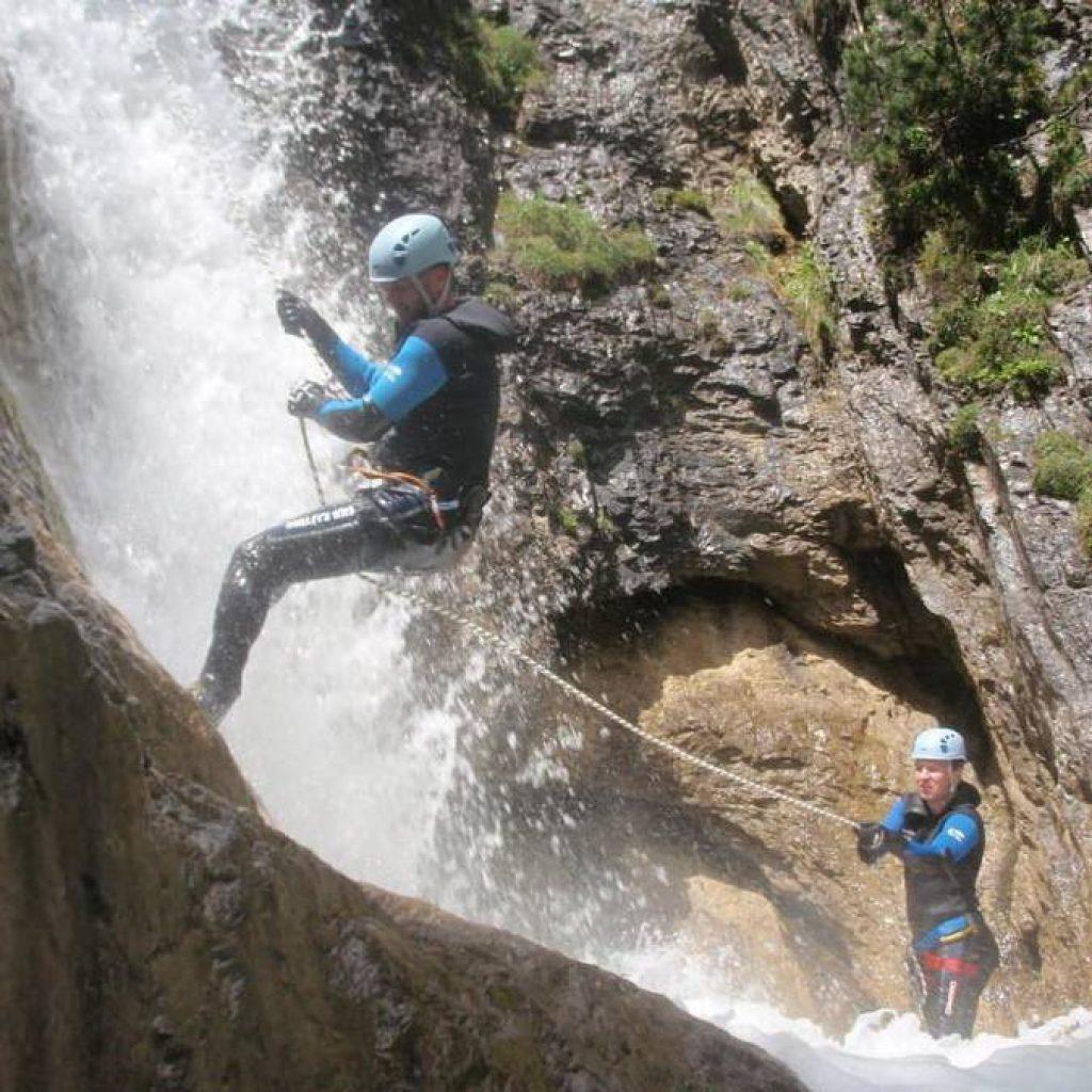 Zwei Menschen seilen sich beim Canyoning ab