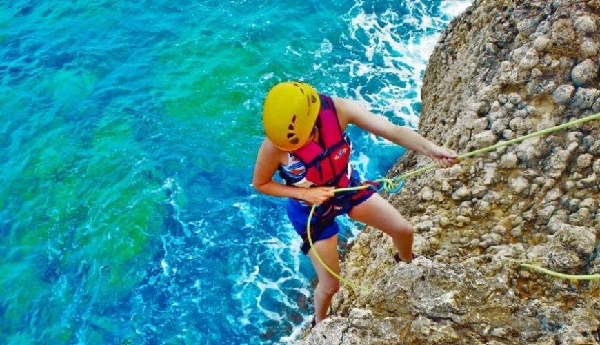 Frau seilt sich an Fels über dem Meer ab