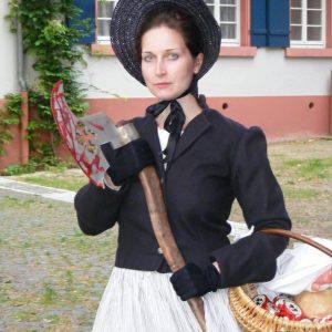 Frau im Kostüm mit blutverschmierter Axt