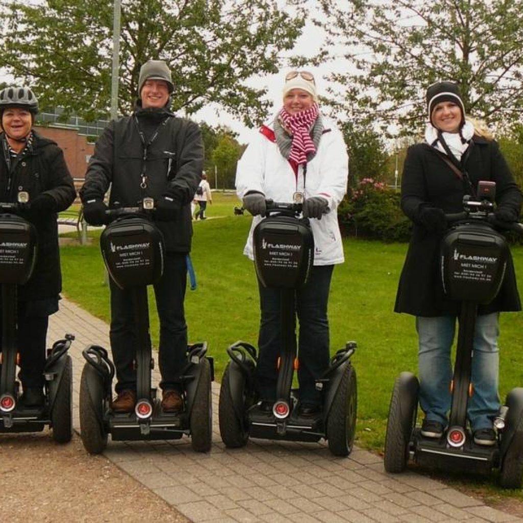 Vier Segwayfahrer nebeneinander in einem Park