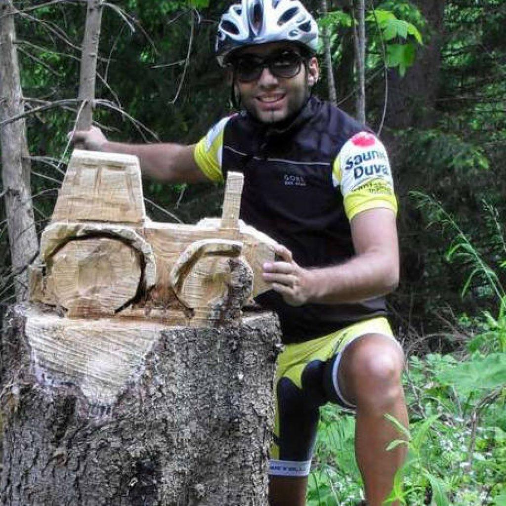 Mountainbikefahrer kniet vor geschnitztem Traktor
