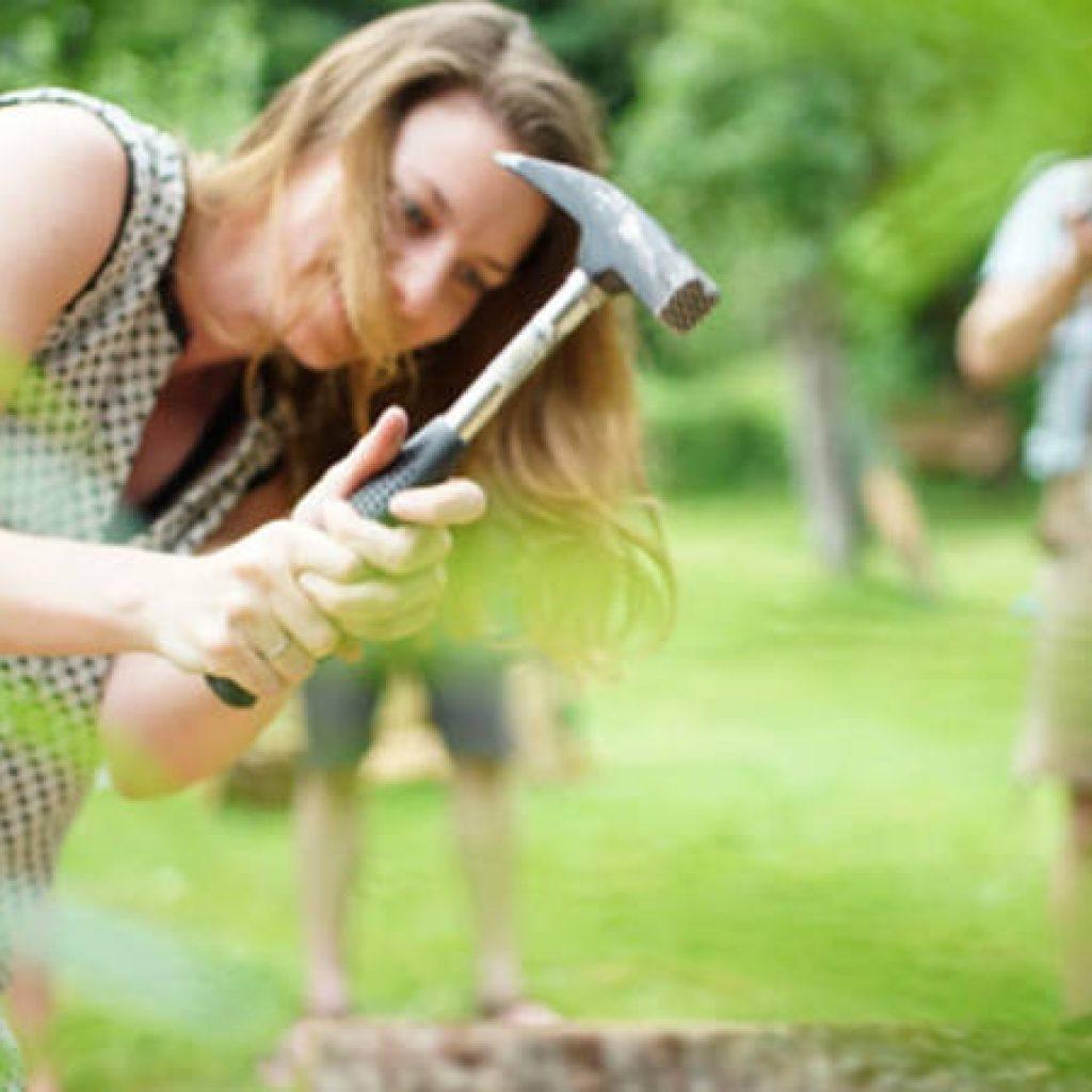 Frau schlägt Nägel mit dem Hammer in Holz
