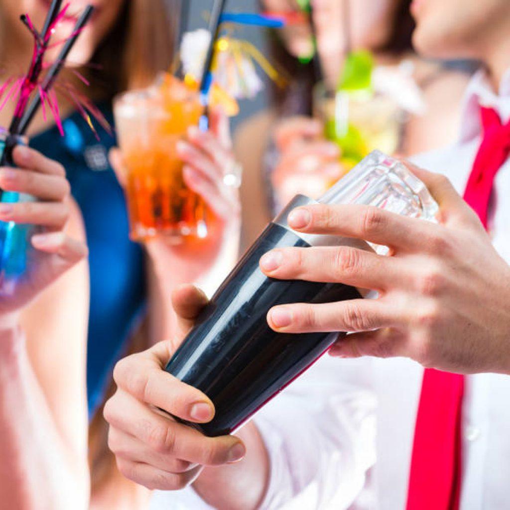 Feiernde Menschen mit Shaker in der Hand