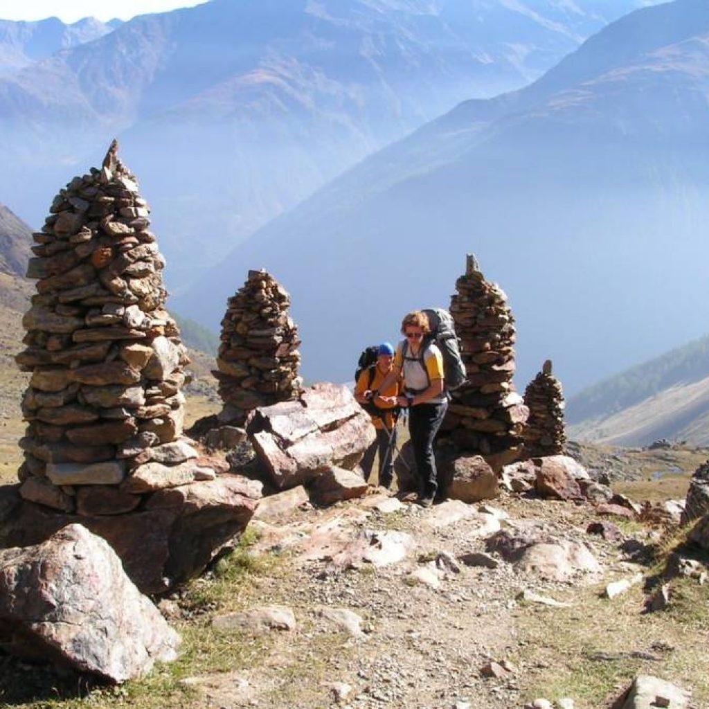 Zwei Wanderer auf dem E5 zwischen geschichteten Steinen