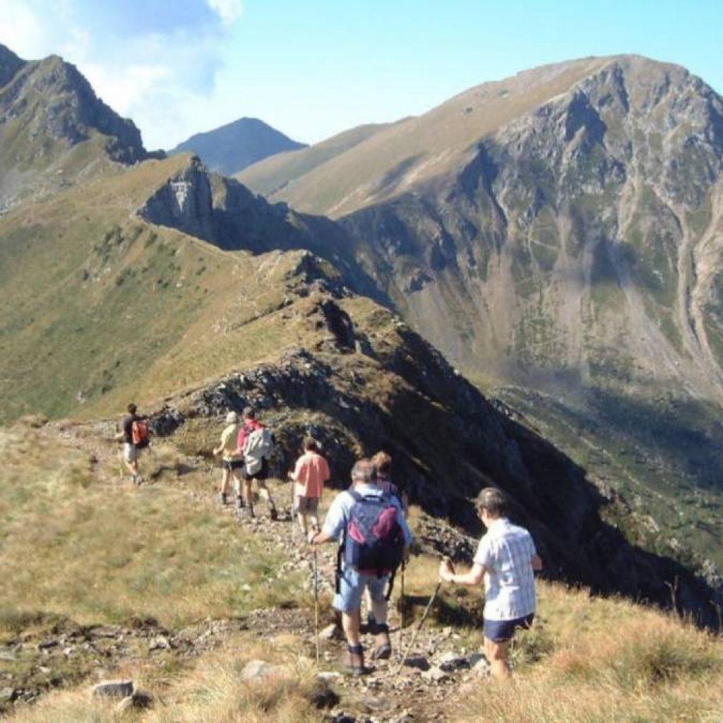 Teilnehmer einer Alpenüberquerung auf einem schmalen Grat