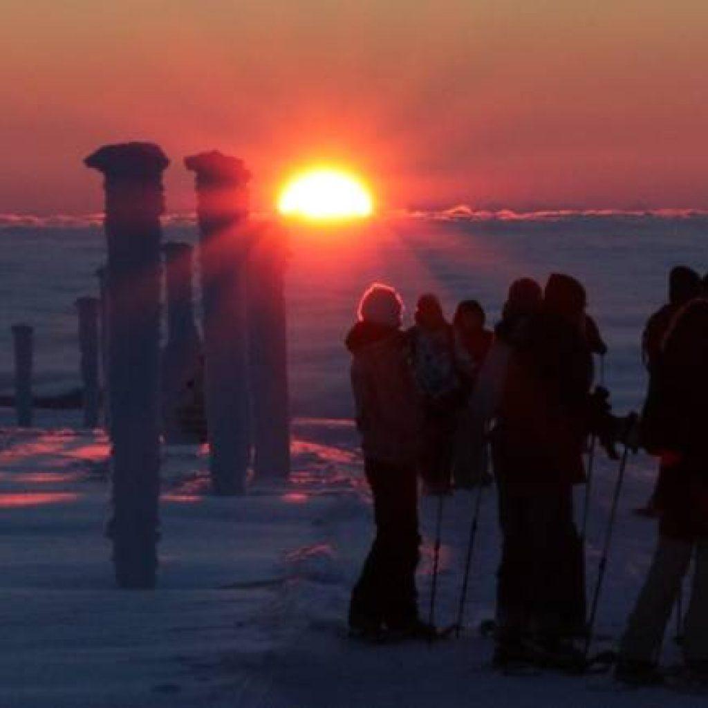 Schneeschuhwanderer beobachten den Sonnenaufgang