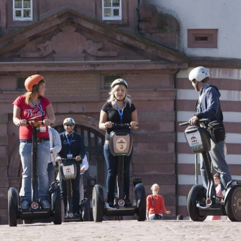 Segwayfahrer vor historischem Sandsteingebäude