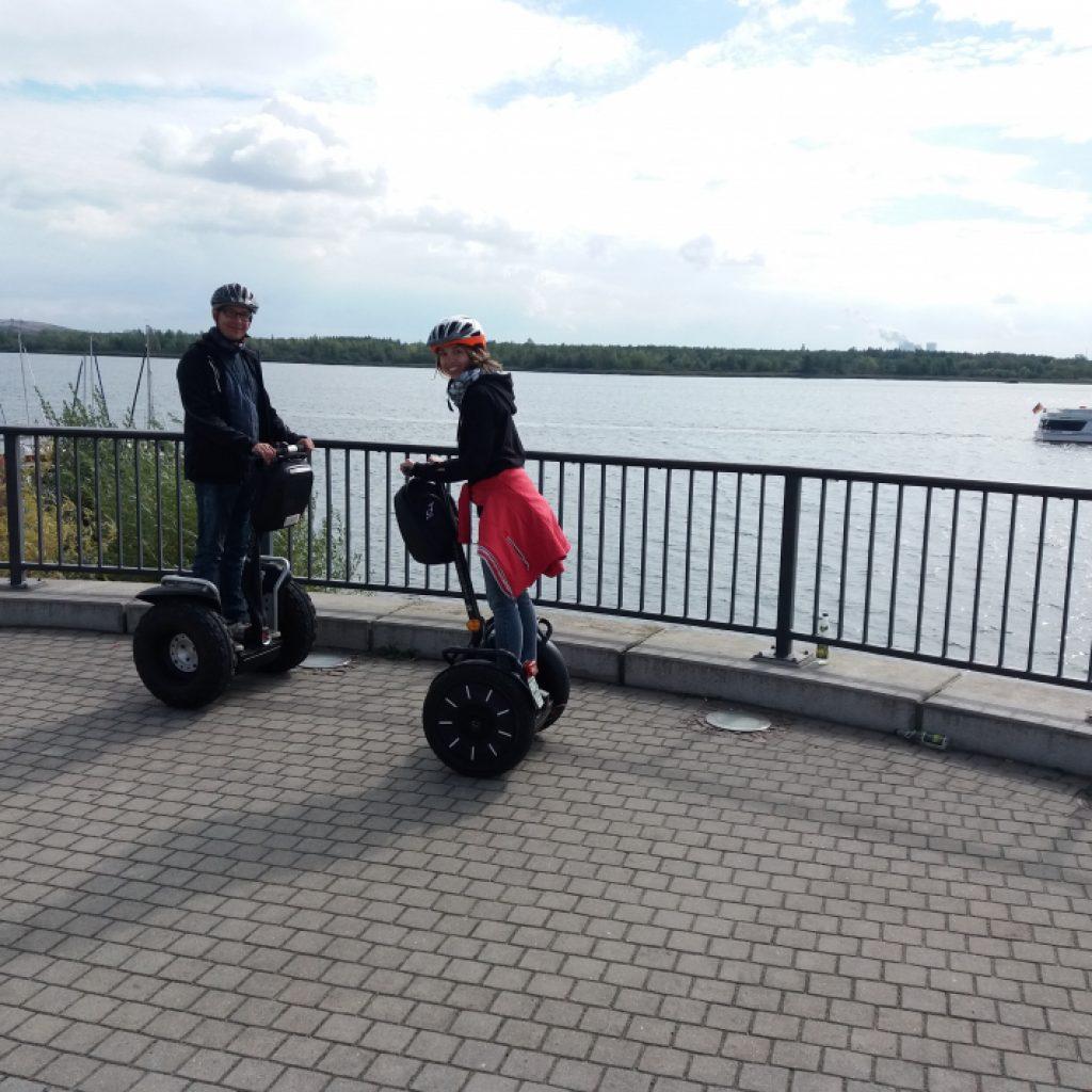 Zwei Segwayfahrer auf einem Aussichtspunkt am See
