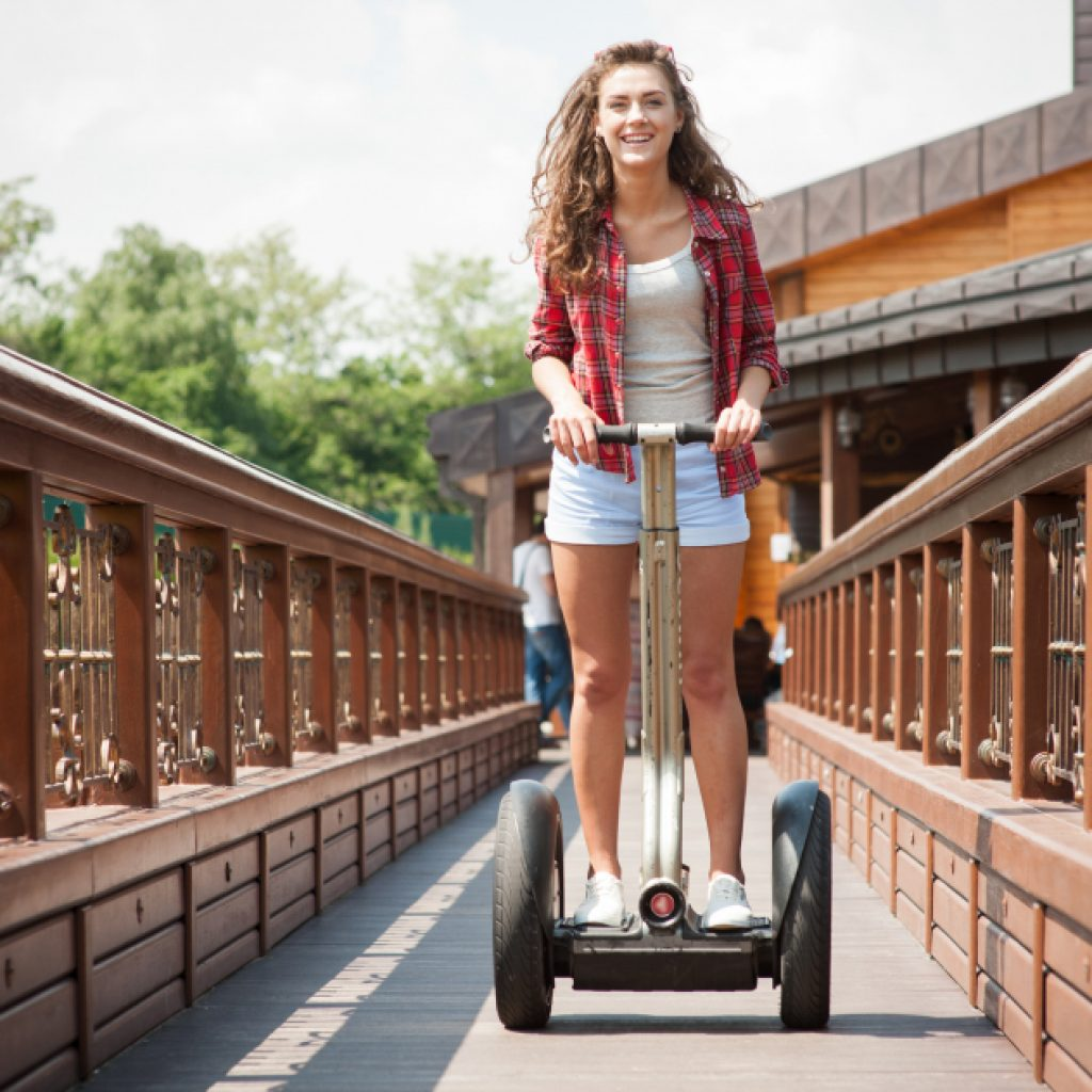 Junge Frau auf Segway auf einer Brücke