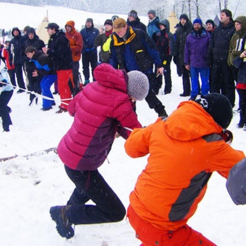 Menschen beim Tauziehen im Schnee