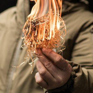 Hand mit angezündeter Holzwolle