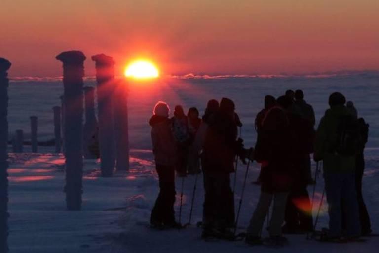 Gruppe von Schneeschuhwanderern beim Sonnenaufgang