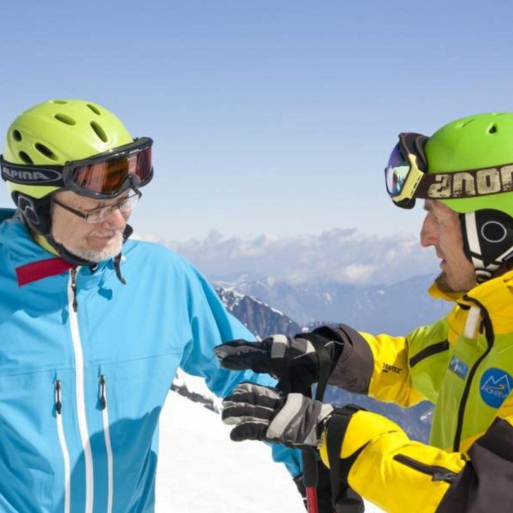Skilehrer und Kursteilnehmer im Gespräch